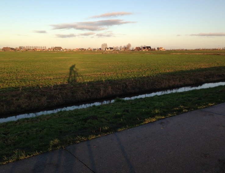 Foto zonnig Fries landschap met schaduw fietser