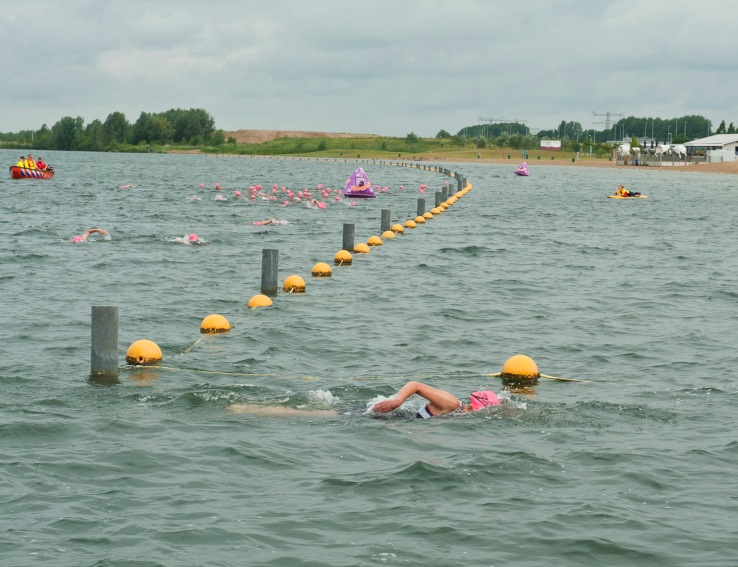 Zwemsters met roze badmutsen langs boeienlijn