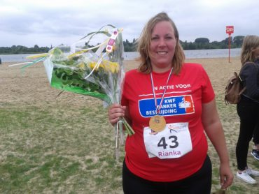 Rianka in KWF-shirt na de finish met bloemen